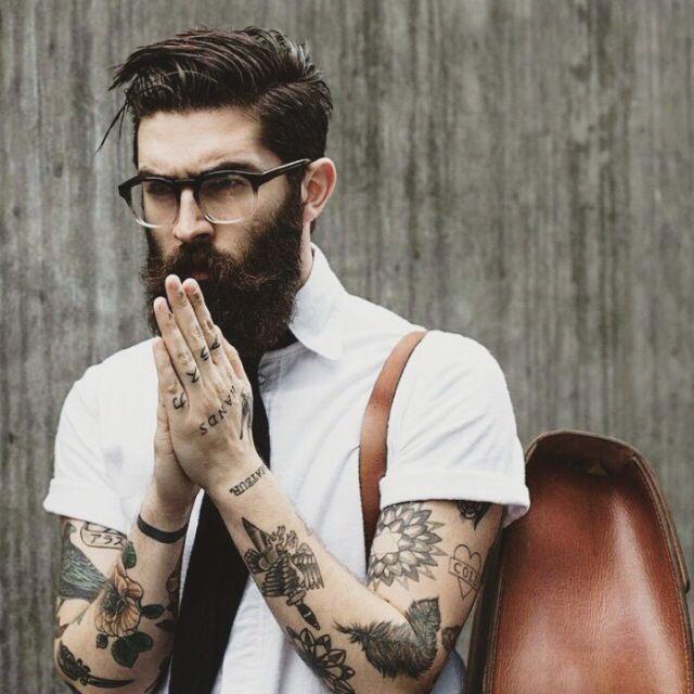 chico con barba y tatuajes en los brazos