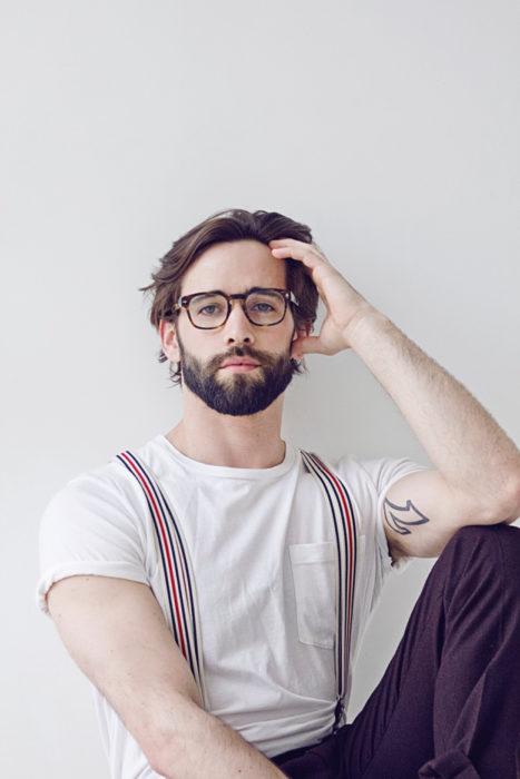chico con barba y cabello largo usando tirantes