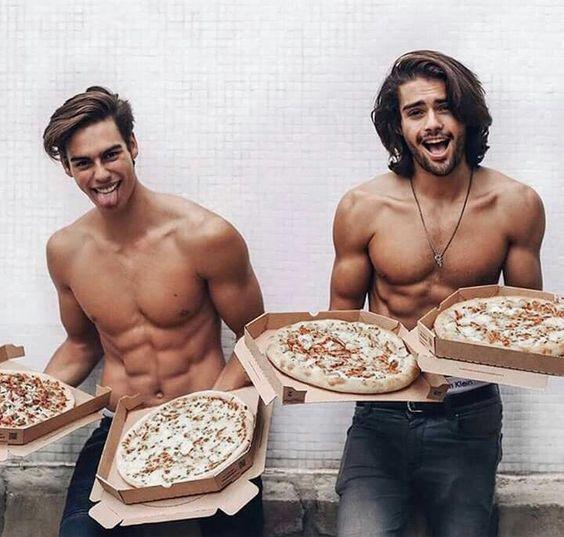 chicos sin camisa llevando pizza