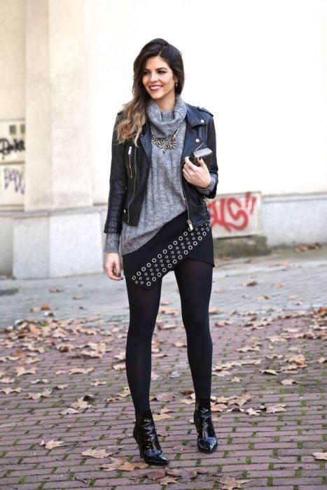 Chica usando un look negro con bootines de charol