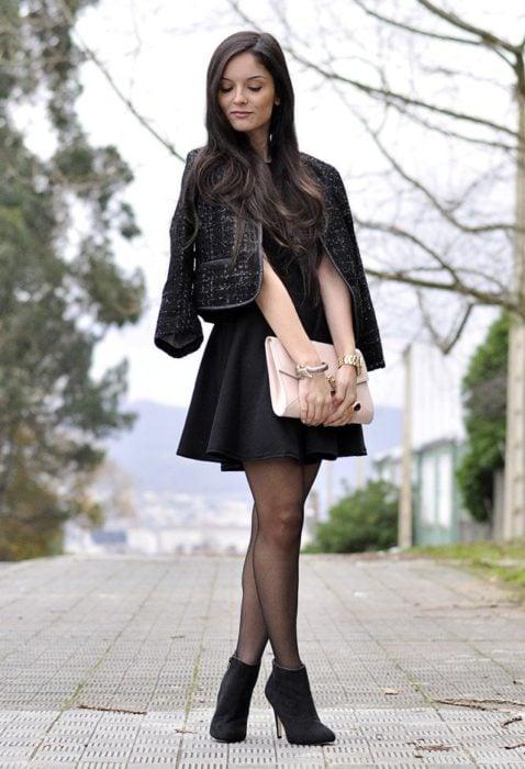 Chica usando botines con medias negras y vestido