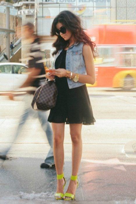 Chica usando un vestido negro y chaleco de mezclilla