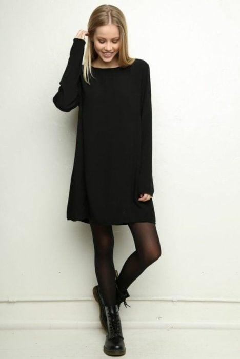 Chica usando un vestido negro y botas militares