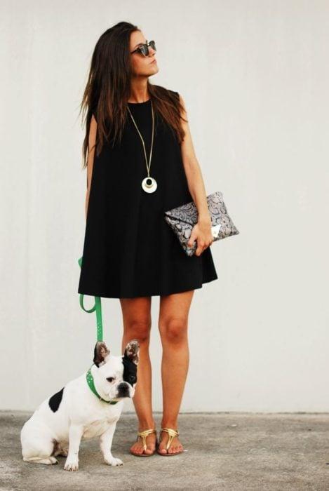 Chica usando un vestido negro y clutch de lentejuelas