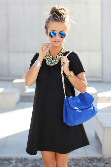 Chica usando un vestido negro y collar de color plata