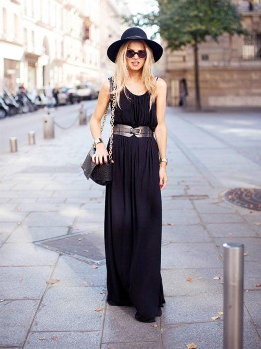 Chica usando un vestido negro con un cinturon marrón