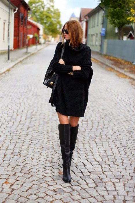Chica usando un vestido negro y botas hasta el muslo