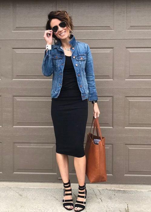 Chica usando un vestido negro y chaqueta de mezclilla