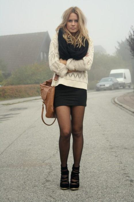 Chica usando un vestido negro y un sueter largo