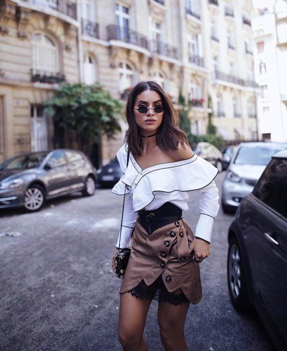 Modelo luciendo unas gafas tiny mientras camina en por Paris