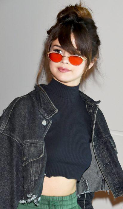 Selena Gomez usando unas tiny sunglases durante una sesión de fotos