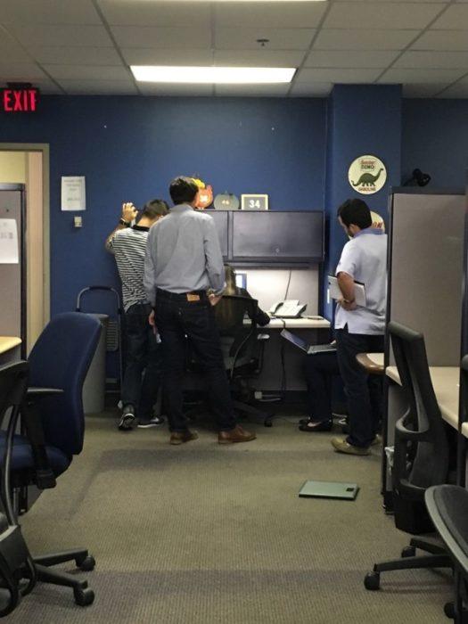 chicos ayudando a una chica en la oficina