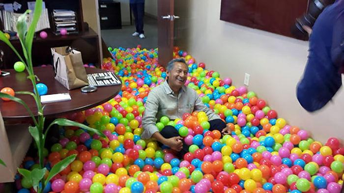 señor jugando en alberca de pelotas