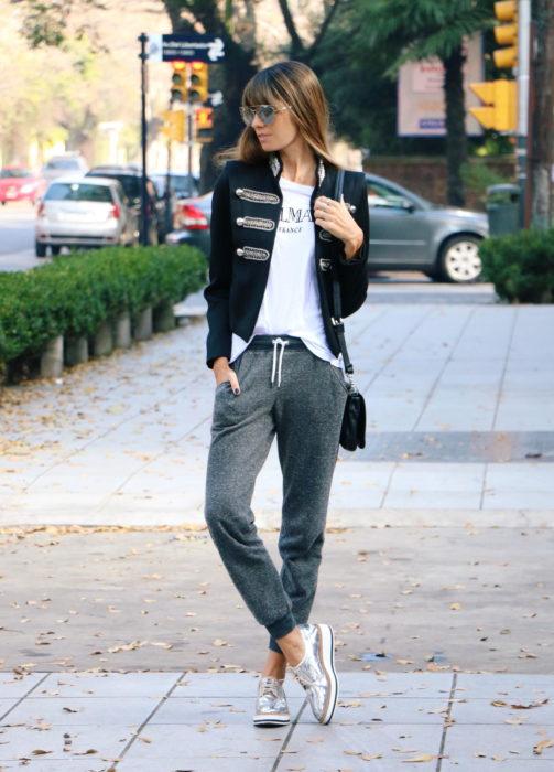 Chica usando unos jogger pants de color gris con una chaqueta de color negro