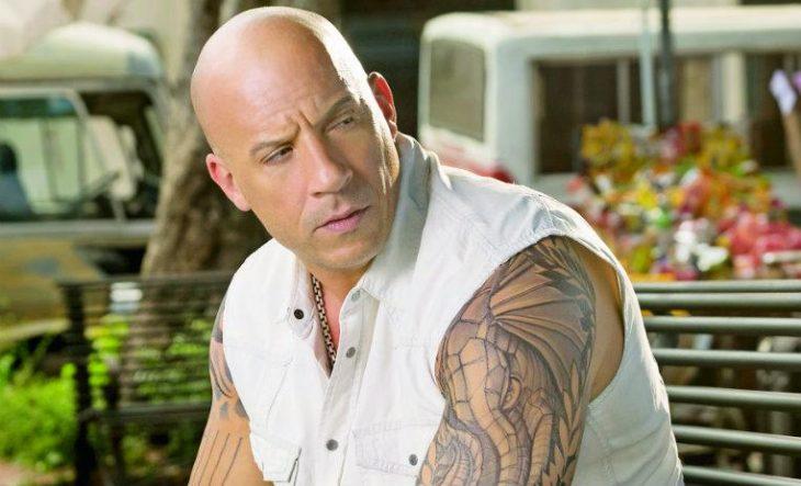 Vin Diesel musculoso usando chaleco blanco, sentado en una banca de un parque con mirada sospechosa
