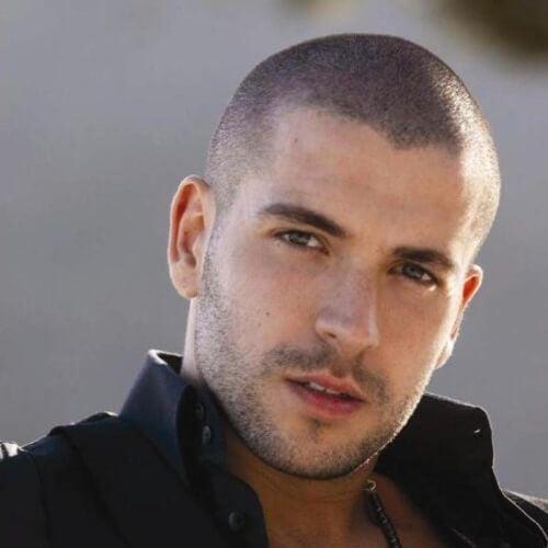 Hombre con cabello súper corto recargado y modelando para una fotografía