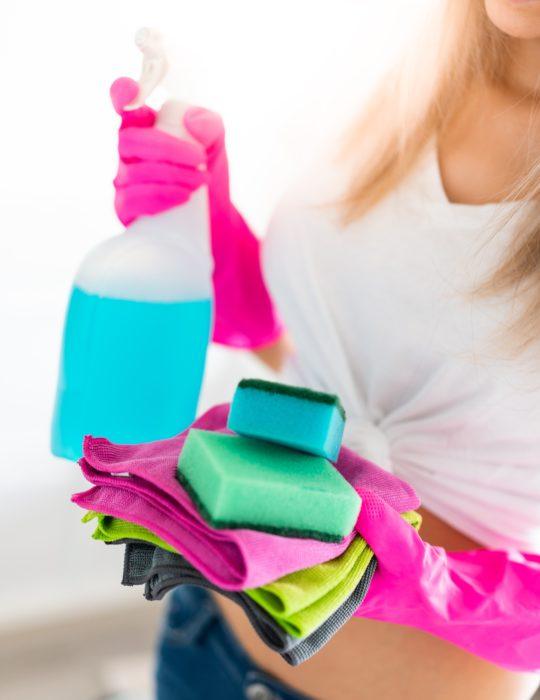 mujer con guantes de limpieza y atomizador y esponjas de limpieza