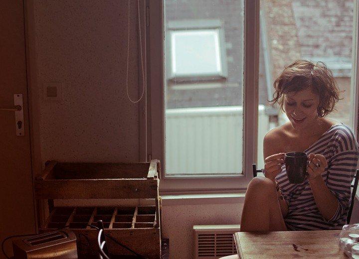 chica tomando café en su departamento