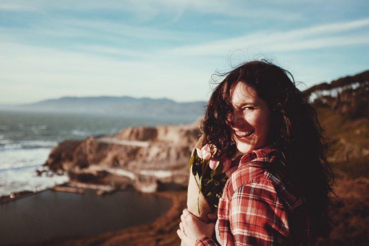 chica sonriendo con flores en mano