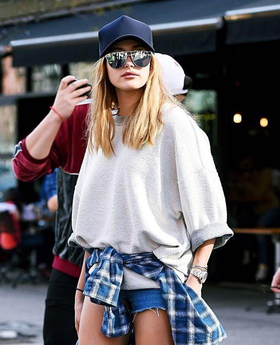 Look con gorras chica usando gorra negra con shorts y sudadera