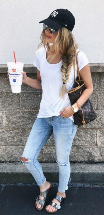 Look con gorras chica usando gorra negra con jeans y blusa blanca