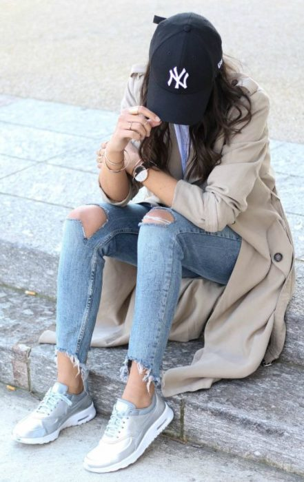 Look con gorras chica usando gorra negra con jeans y gabardina