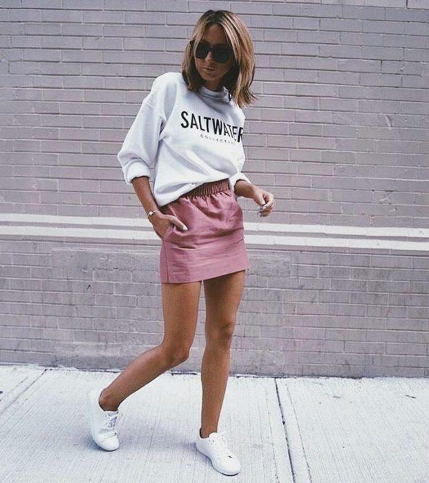 Chica usando un look con sudadera y minifalda