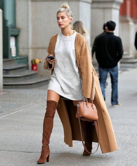 Chica usando un look con sudadera y botas largas