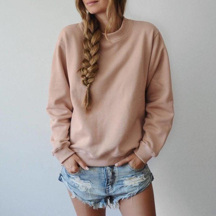 Chica usando un look con sudadera y shorts