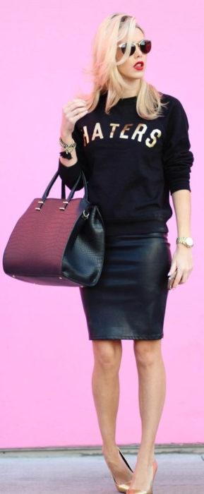 Chica usando un look con sudadera y falda de cuero negra