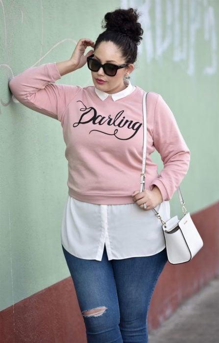Chica usando un look con sudadera sobre una blusa de vestir