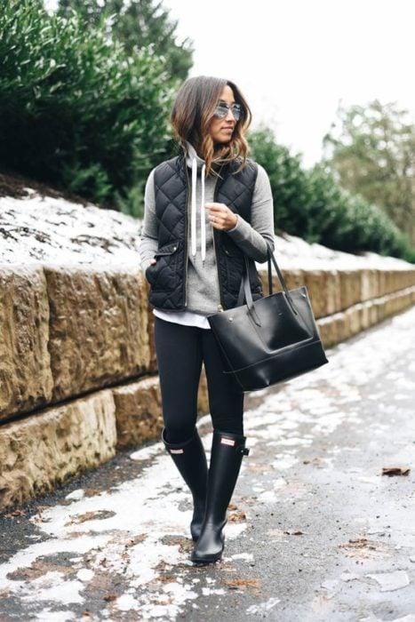 Chica usando un look con sudadera, jeans y botas de lluvia