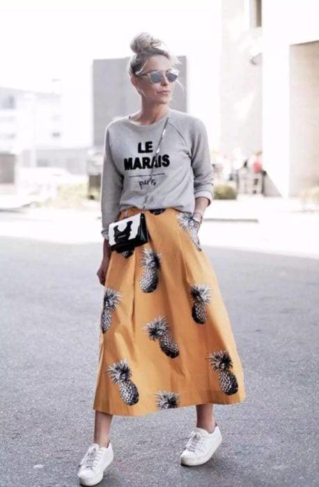 Chica usando un look con sudadera y falda larga