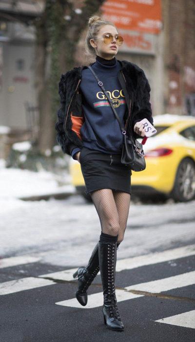 Chica usando un look con sudadera, falda y botas
