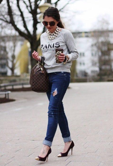 Chica usando un look con sudadera jeans y stilletos
