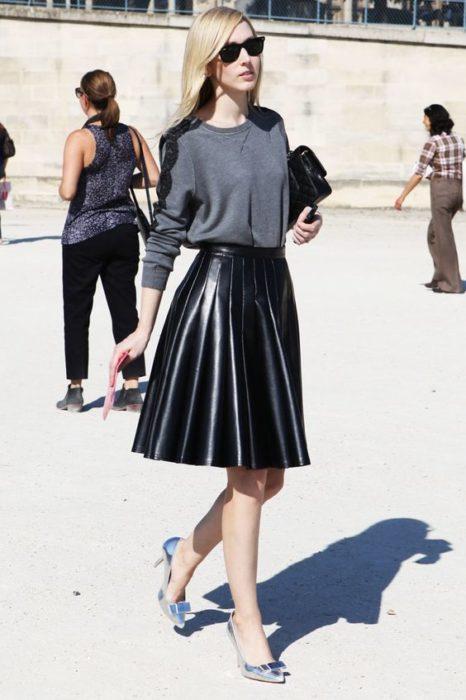 Chica usando un look con sudadera y falda de piel