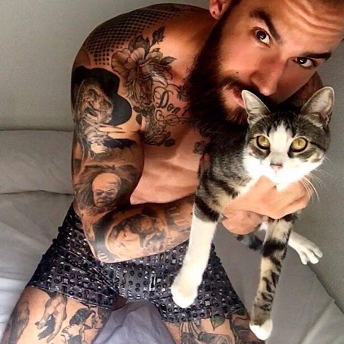 chico cargando un gato