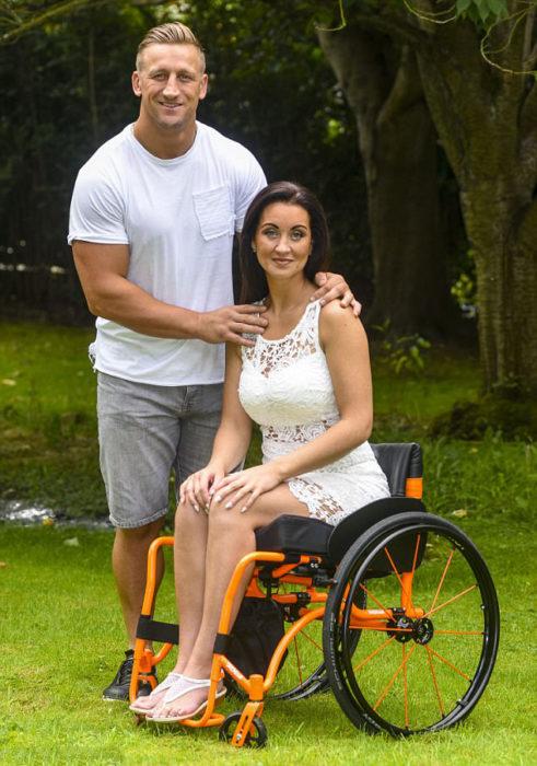 Mujer paralisada en una silla de ruedas junto a su entrenador pesonal