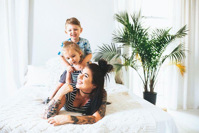 Mujer recostada en la cama mientras juega con sus hijos
