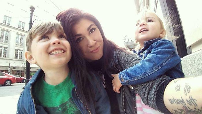 Mujer con sus hijos en la calle riendo