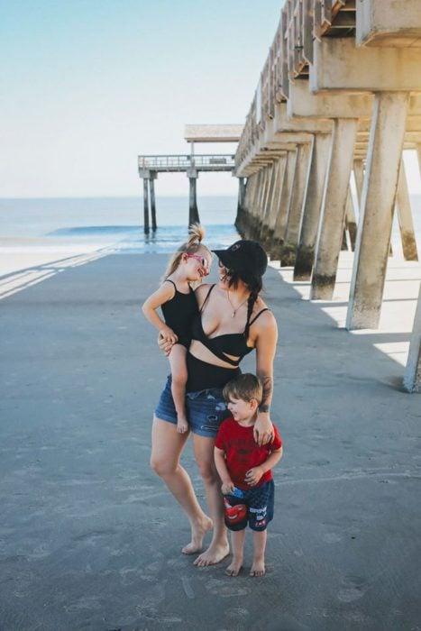 Mujer paseando junto a sus dos hijos en la palaya
