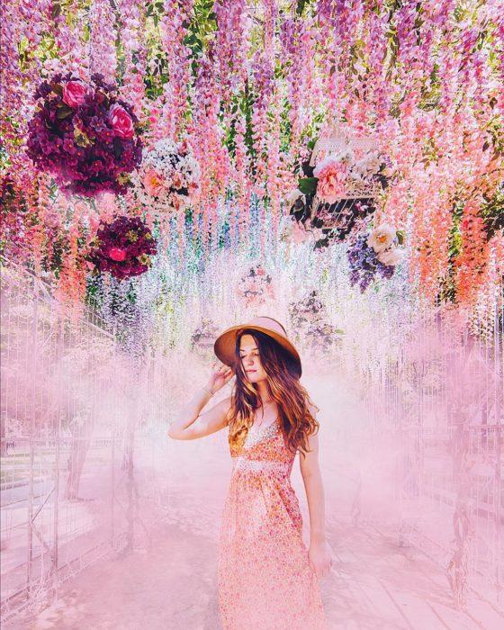 Mujer usando un vestido rosa y posando junto a flores que caen del cielo