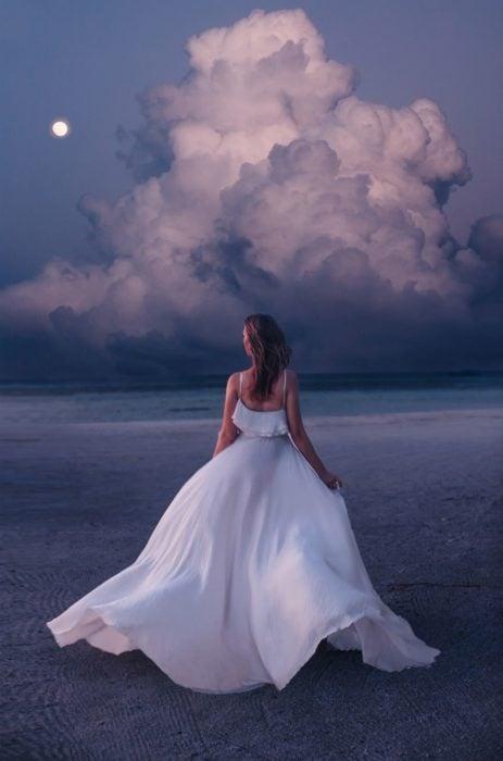 Mujer usando un vestido y posando junto a las nubes