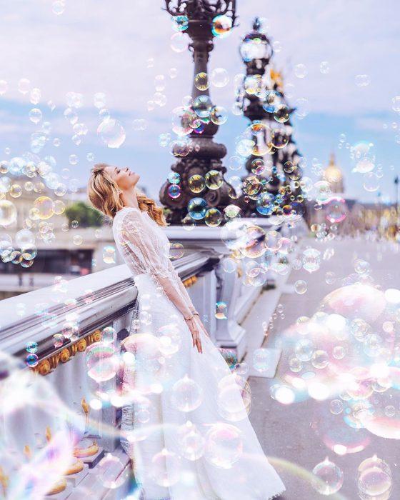 Mujer rodeada de burbujas mientras está parada en un puente