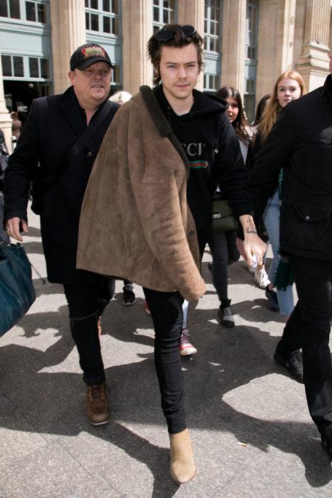 Harry Styles caminando junto a su guardaespaldas