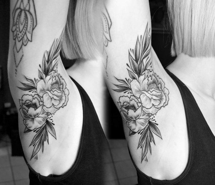 Chica con un tatuaje en la axila de una flor