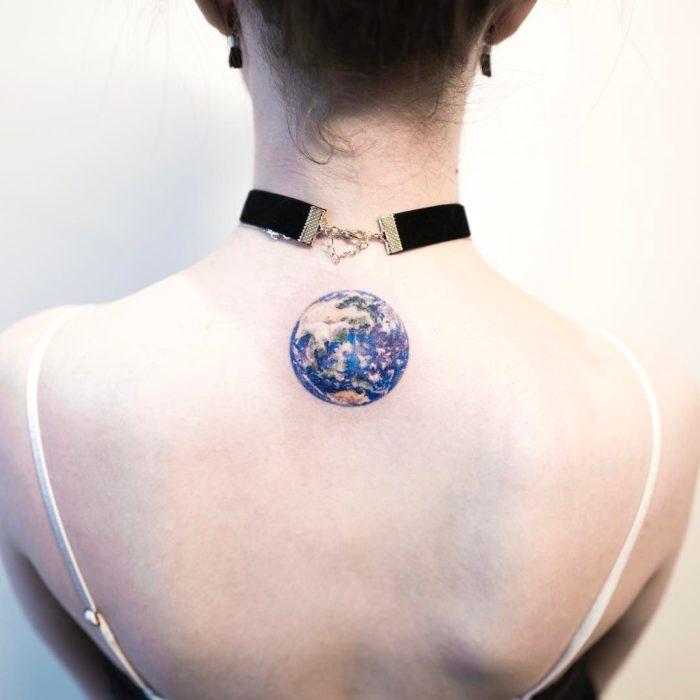 chica con tatuaje del planeta tierra