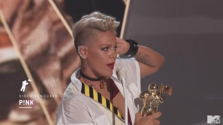 mujer rubia con microfono y premio