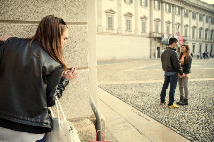 mujer espiando a pareja en la calle