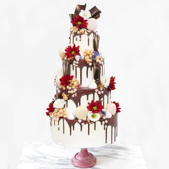 pastel blanco de cuatro pisos y flores rojas